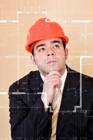 thinks: A custom home builder or architect thinks as he examines the blueprints on the clear glass display in front of him.