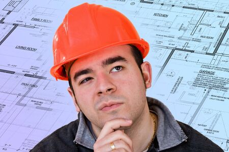 A construction worker or architect wearing a hard hat has a contemplative look on his face with generic blueprints in the background. photo