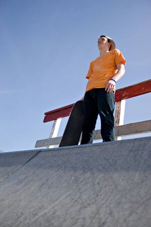 attempting: A young man skateboarding standing at the top of a ramp at the skate park prior to attempting a trick. Stock Photo