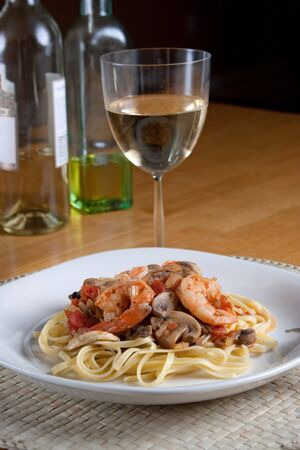 scampi: A delicious shrimp scampi over linguine dish along with a glass of pinot grigio white wine.  Stock Photo