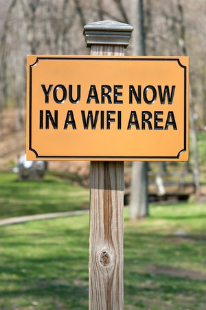 hotspot: A sign that reads YOU ARE NOW IN A WIFI AREA indicating a wireless hotspot for internet use. Stock Photo