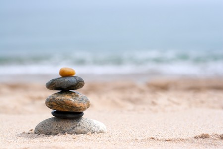 A pile of round smooth zen rocks stacked in the sand at the\ beach.