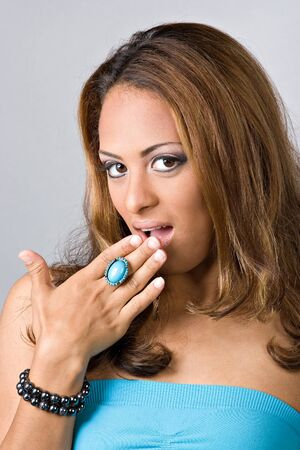 A flirty Spanish woman covering her mouth out of surprise. photo