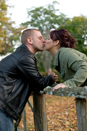 smooch: A young happy couple passionately kissing each other outdoors in the fall.