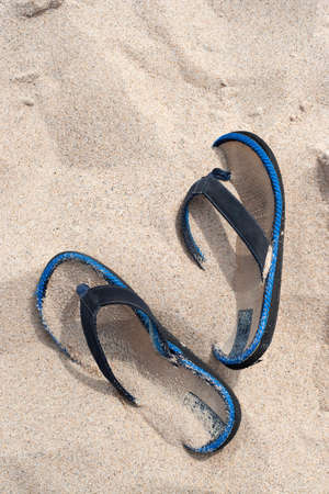 A pair of flip flops or sandals buried in the sand at the beach. Stock Photo - 6891880