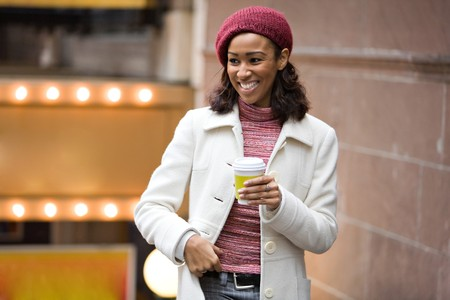 An African American business woman is walking through the city holding a cup of coffee tea or cappuccino. photo