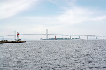 The Newport Rhode Island area Claiborne Pell bridge as seen from a distance on a hazy day along with the lighthouse on Goat Island.  The 70th longest suspension bridge in the world. photo