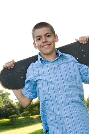 early teens: A boy in his early teens happily posing with his skateboard.