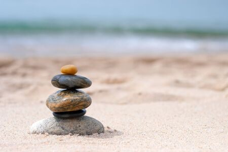 A pile of round smooth zen rocks stacked and balancing in the sand at the beach.  photo