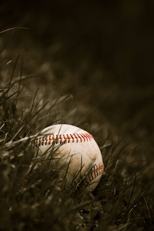 hardball: One aged and worn grungy baseball sitting in the green grass in sepia tone.