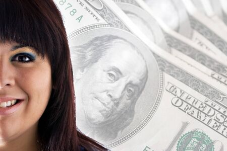 A rich or successful smiling woman in front of a money background with copy space for your text. photo