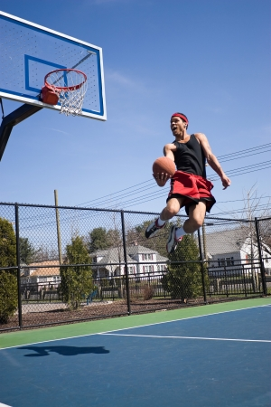 dunk: A young athlete flying through the air towards the basketball hoop for a lay up or slam dunk.