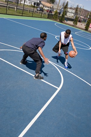 layup: A young basketball player guards his opponent during a one on one basketball game at the park.