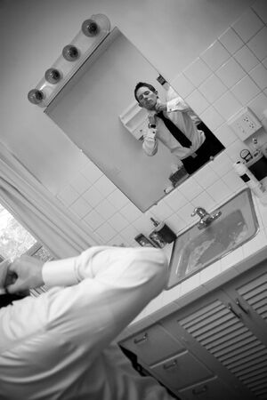 bathroom mirror: A man in a shirt and tie in the bathroom getting ready to go.  Shallow depth of field.
