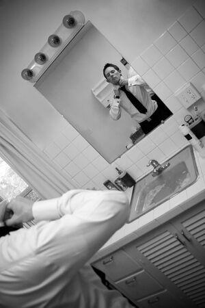 Un uomo in una camicia e cravatta in bagno sempre pronto ad andare. Poca profondità di campo.