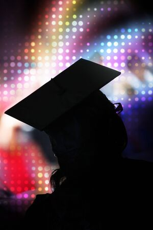 A recent university or high school graduate posing in her cap and gown in front of a rainbow halftone background. photo