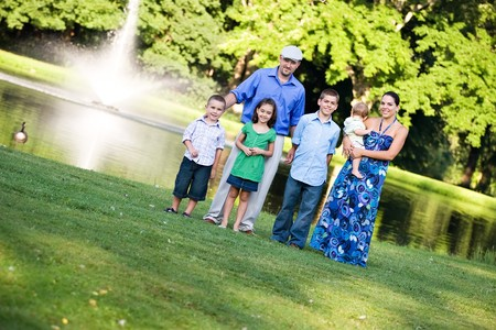 An attractive young family together at the park on a nice spring or summer day. photo