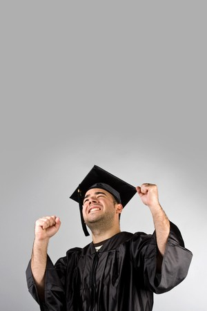 A recent graduate posing in his cap and gown and celebrating.  Isolated over a silver background with copy space. photo