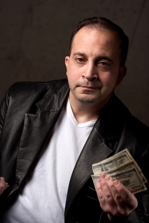 A middle aged man wearing a leather jacket holding a handful of one hundred dollar bills. Shallow depth of field. photo