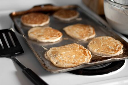 flapjacks: Apple pancakes cooking on the hot stove griddle.  Shallow depth of field. Stock Photo