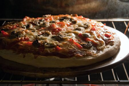 A fresh homemade mushroom and pepper pizza fresh out of the oven and ready to slice. Shallow depth of field. 스톡 콘텐츠