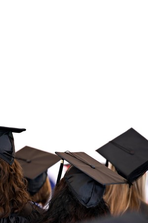 A group of college or high school graduates wearing the traditional cap and gown isolated over white.  Plenty of copy space for your text or layout.  Shallow depth of field.