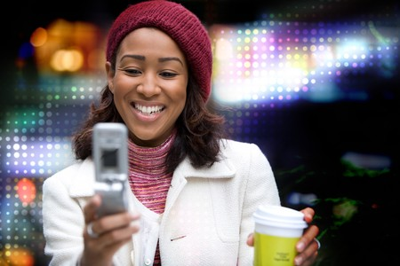 A beautiful African American business woman checking her cell phone in the city.  She could be text messaging or even browsing the web via a wireless broadband signal.