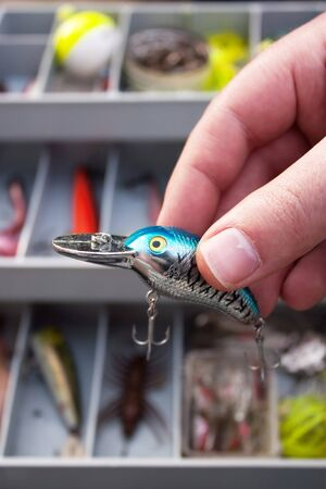 A fisherman selects just the right lure from his tackle box that he is going to fish with. photo