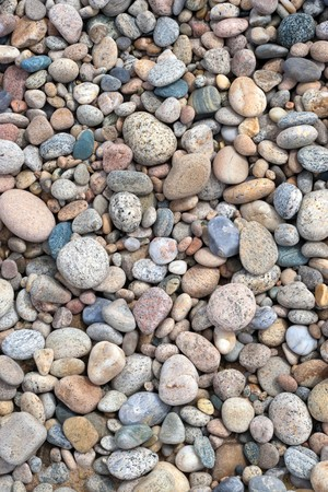 A close up view of smooth polished stones washed ashore on the beach.