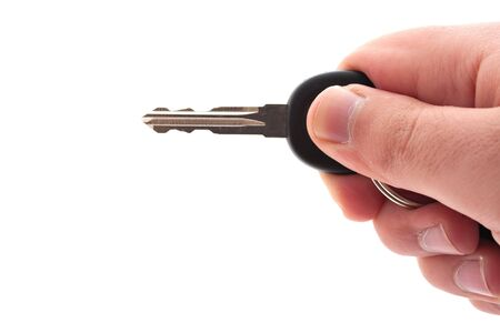 A hand holding a car or house key isolated over a white background. photo