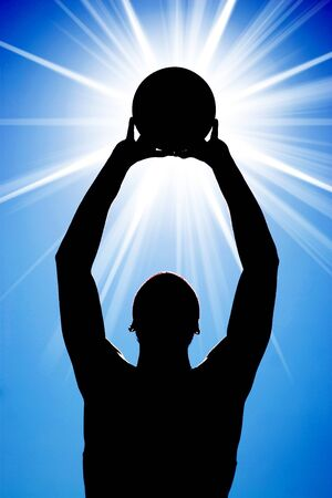 A silhouette of a basketball player holding up a ball in front of a bright glowing lens flare. photo