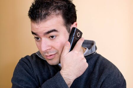 A young man talking on his cell phone.  He is holding the phone with his right hand but listening with his left ear. photo