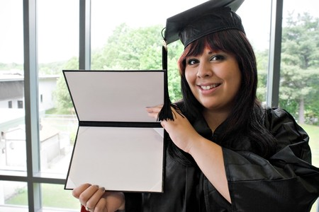 A student that recently had a school graduation posing proudly with her diploma indoors. photo
