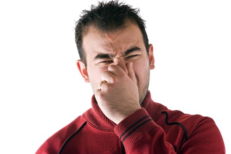 A young man holds or pinches his nose shut because of a stinky smell or odor. photo