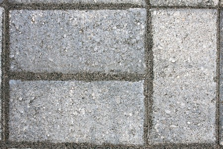 Closeup of three paver bricks in a paved stone patio floor. photo