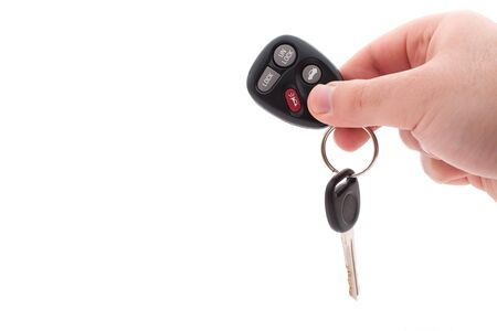 A hand holding car keys and a remote control for keyless entry isolated over white. photo