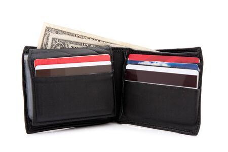 A black leather wallet with a few dollars and a bunch of credit cards isolated over white. photo