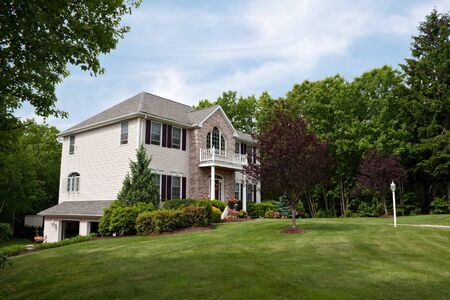 A modern custom built luxury home with a two car garage in a residential neighborhood.  This high end house is very nicely landscaped property.