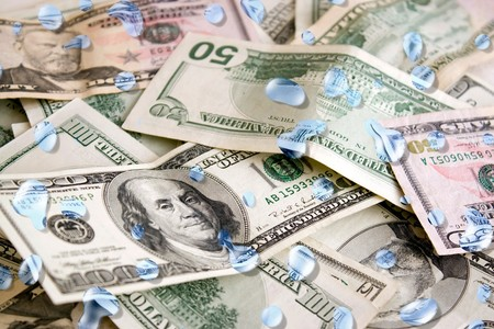 hard rain: A pile of US dollars with blue water droplets on them.  Great concept for money laundering or rainy day savings spending.  Stock Photo