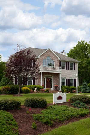 A modern custom built luxury house in a residential neighborhood.  This upper class home is a very nicely landscaped property. Stock Photo - 7106459