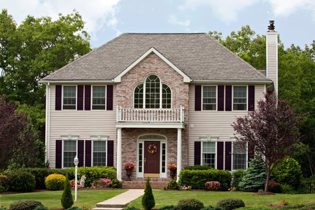 A large custom built luxury house in a residential neighborhood.  This high end home is a very nicely landscaped property. Stock Photo - 7106460
