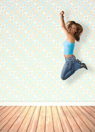 A young woman jumping in the air indoors in front of an interior decorated with vintage wallpaper. photo
