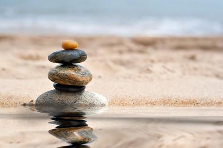 Een stapel van ronde glad zen als stenen gestapeld in het zand op het strand met een spiegel reflectie van een pool van water.