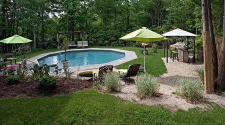 A wide angle panoramic view of a luxurious in ground pool and patio.  This partly wooded backyard offers the same level of luxury found in many vacation resorts. photo