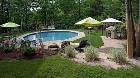 Een groot hoek panorama van een luxe in grond zwembad en terras. Dit onder meer beboste achtertuin biedt hetzelfde niveau van luxe te vinden in veel vakantie resorts.  Stockfoto
