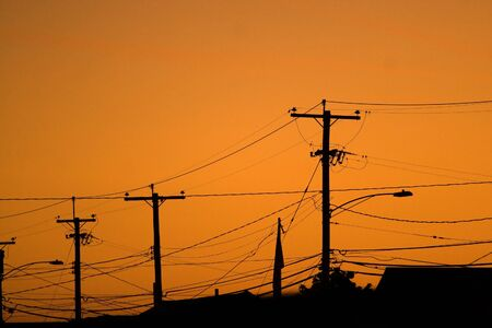 residential neighborhood: Silhouettes of the power lines and wires in a residential neighborhood backlit by the evening sky. Stock Photo