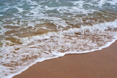 ashore: Closeup detail of the foaming sea waves washing ashore at the beach. Stock Photo