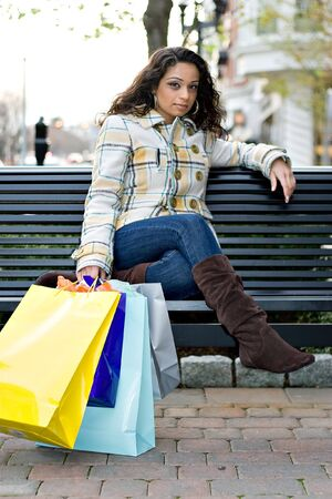 A young Indian woman taking a break on a park bench while out shopping in the city. Stock Photo - 7299945