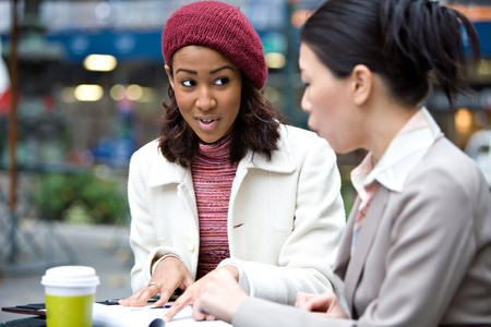 Two business women having a casual meeting or discussion in the city. Shallow depth of field. photo