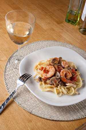 pinot grigio: A delicious shrimp with linguine pasta dish and a nice glass of pinot grigio white wine.